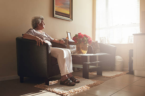 Senior woman sitting alone on a chair at home.