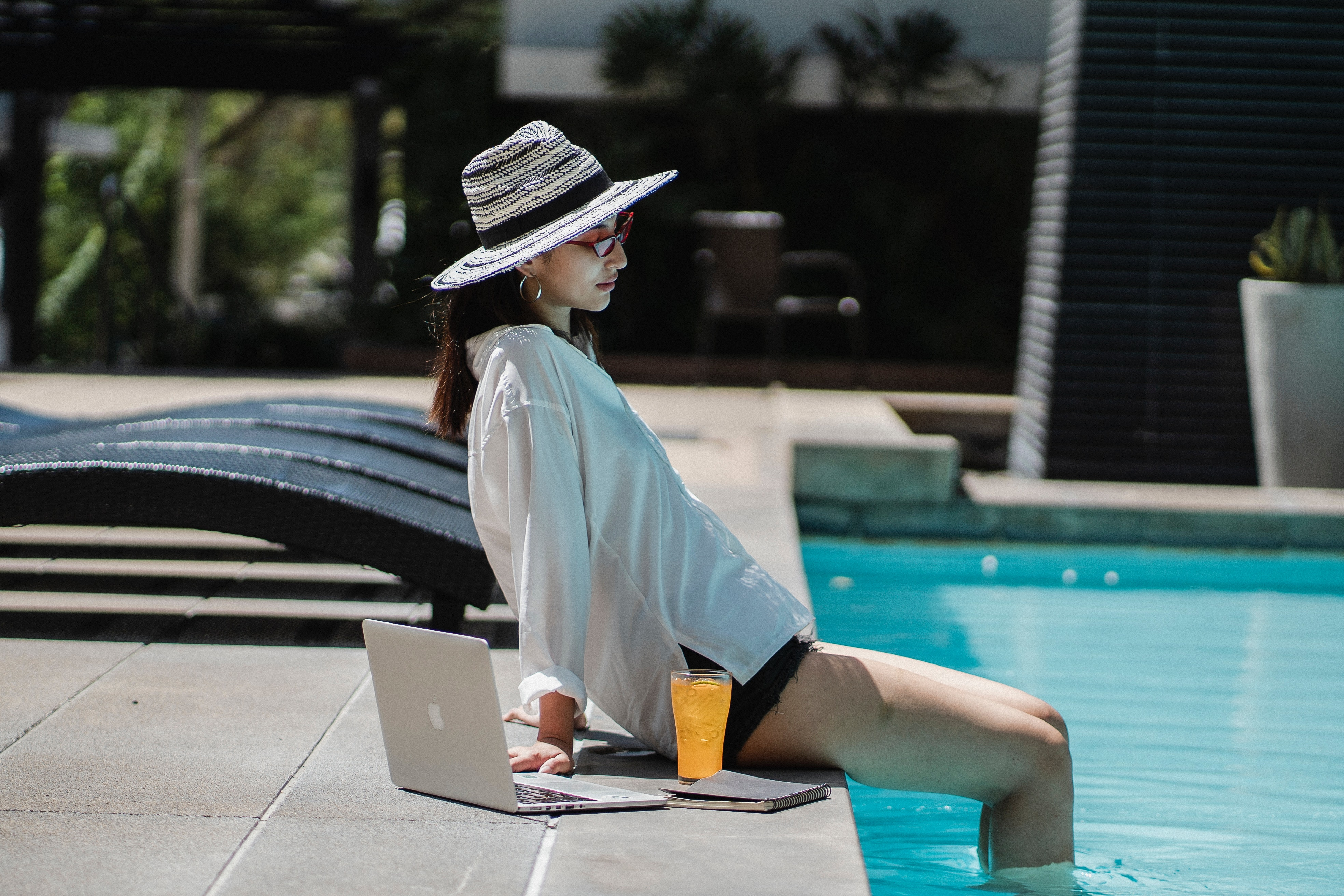Woman relaxing by pool with laptop