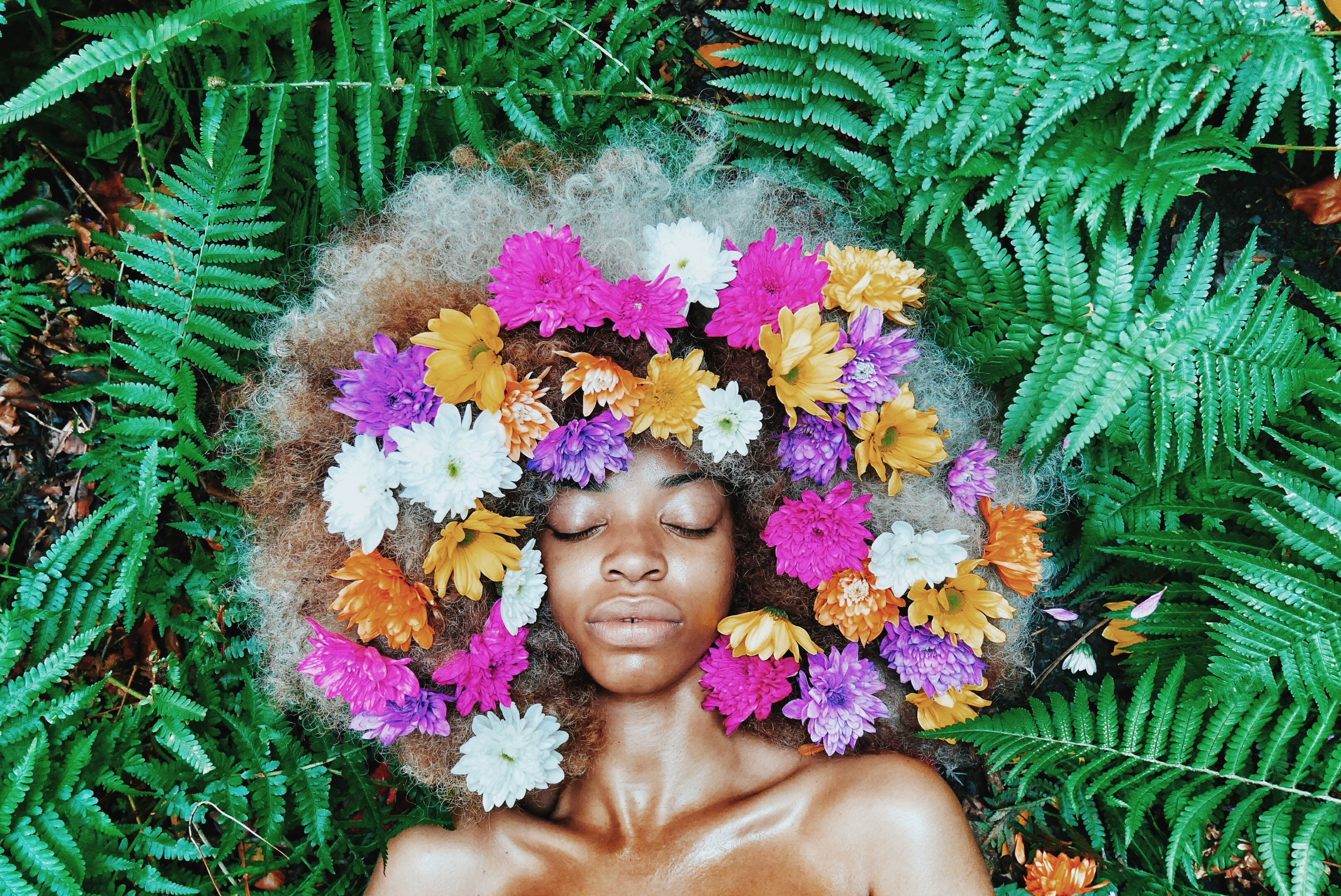 Black woman with flowers in her hair surrounded by plants.