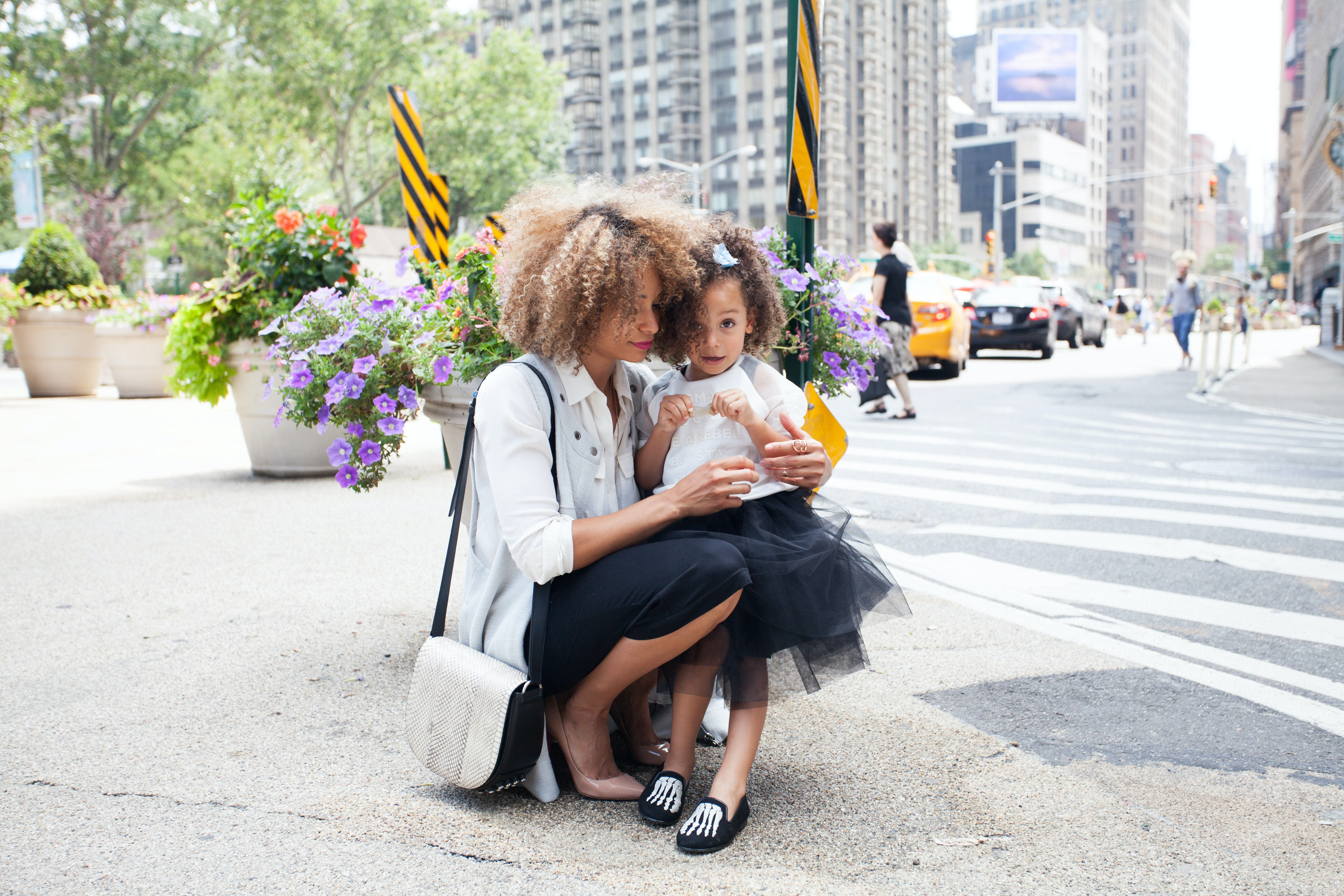 Working Black mom kneeling with daughter on city street