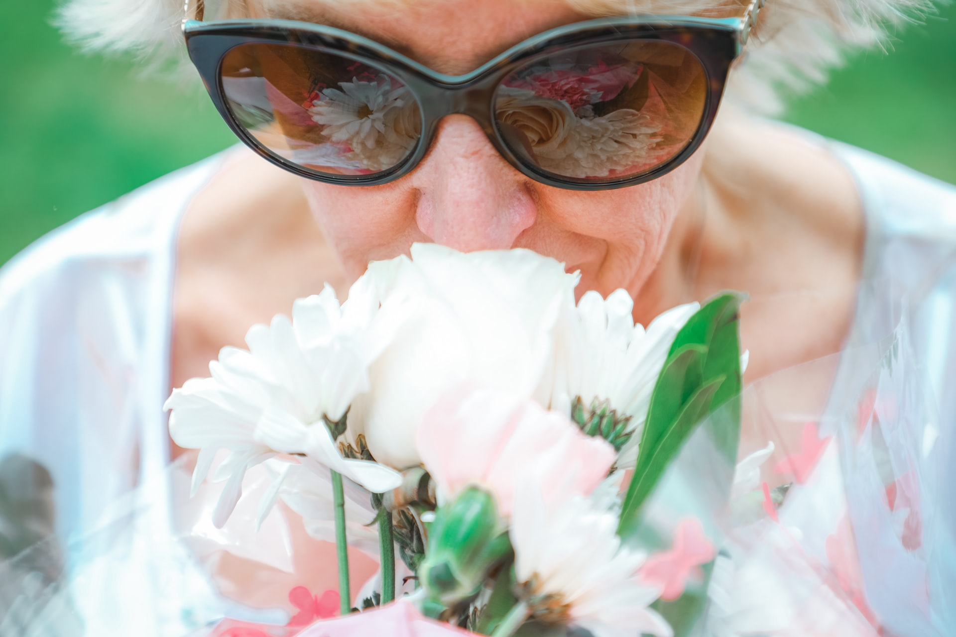 old woman wearing sunglasses smelling flowers