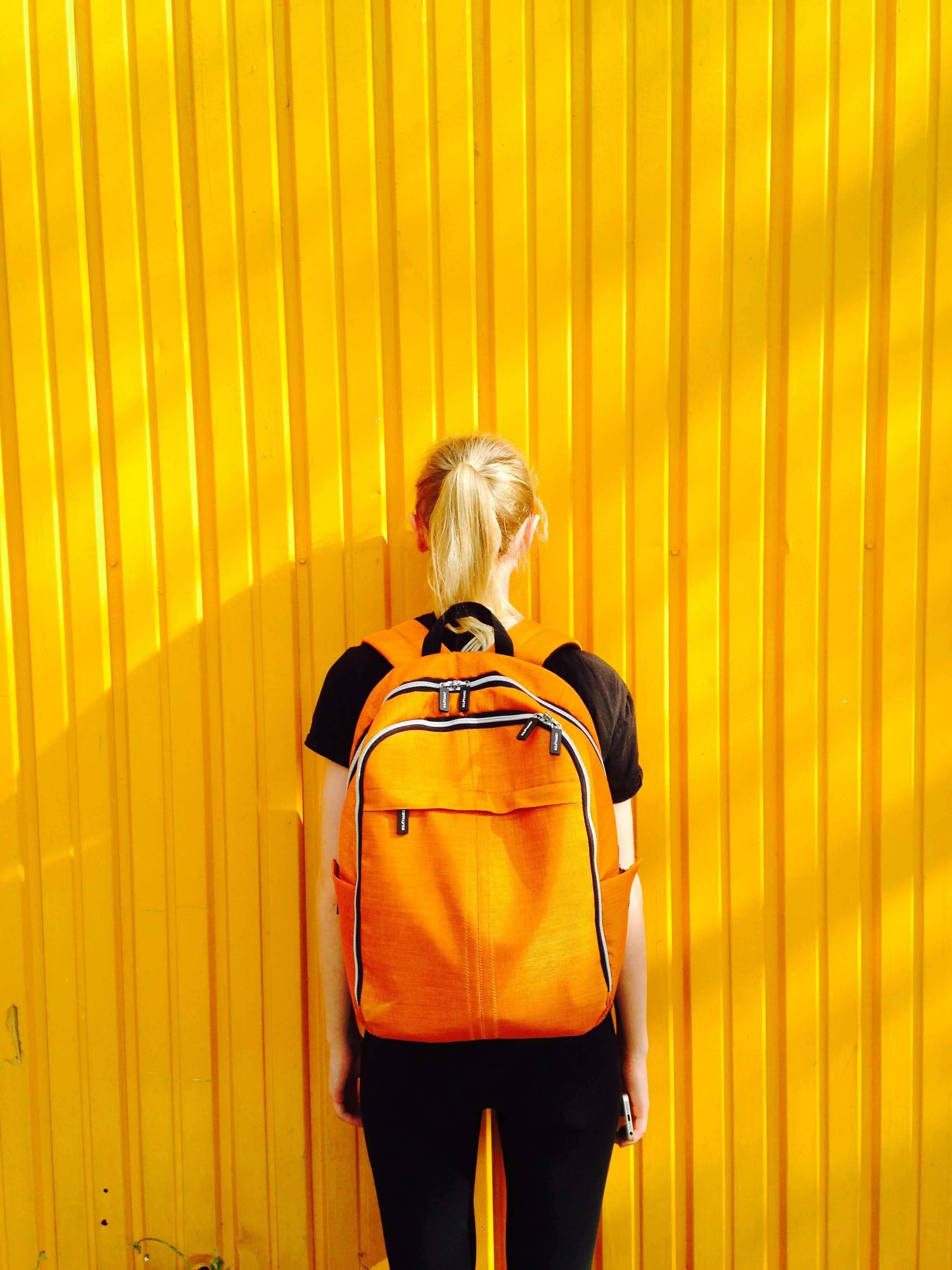 Woman with backpack on facing a yellow wall