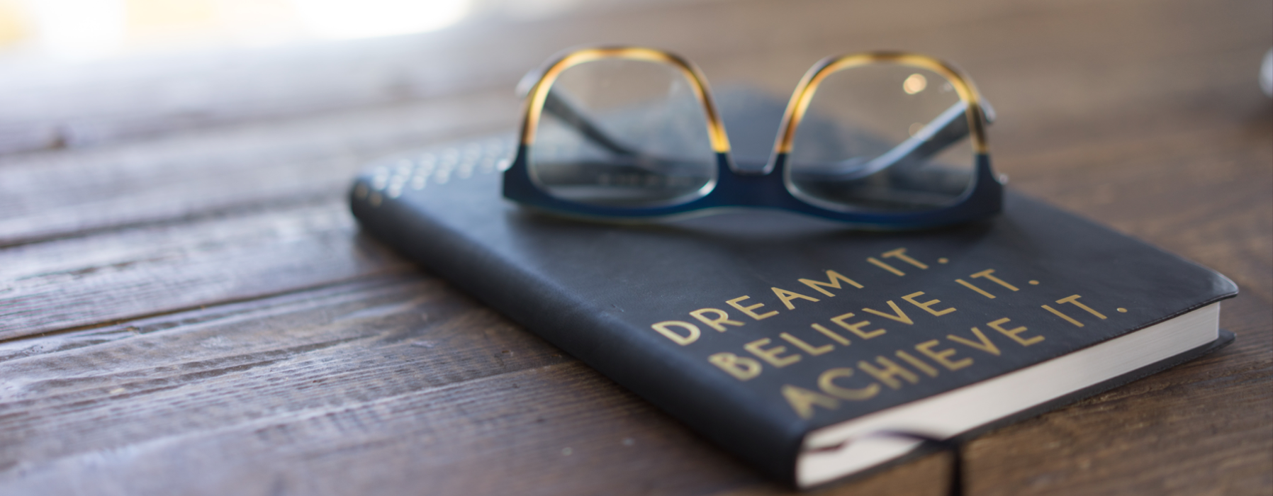"""Glass on top of journal reading """"Dream it. Believe it. Achieve it."""" Photo for Unsplash by Carolyn Christine."""