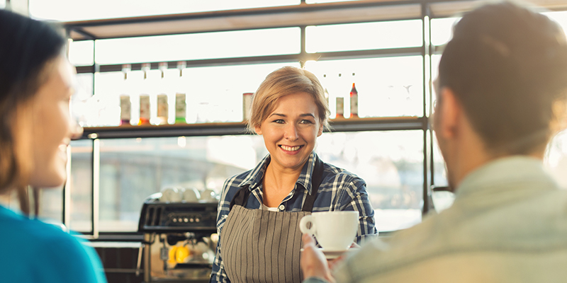 Happy smiling barista making coffee and talking to her guests at bar counter. Experienced female bartender welcoming couple. Small business, occupation people and service concept, copy space