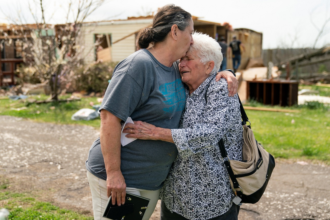 Mary Umetsu, left, and family friend Carol Cunningham, right, embrace each other as Cunningham becomes emotional outside Umetsu's damaged home the day after a string of tornadoes caused several fatalities in Ohatchee, Alabama, U.S., March 26, 2021. REUTERS/Elijah Nouvelage