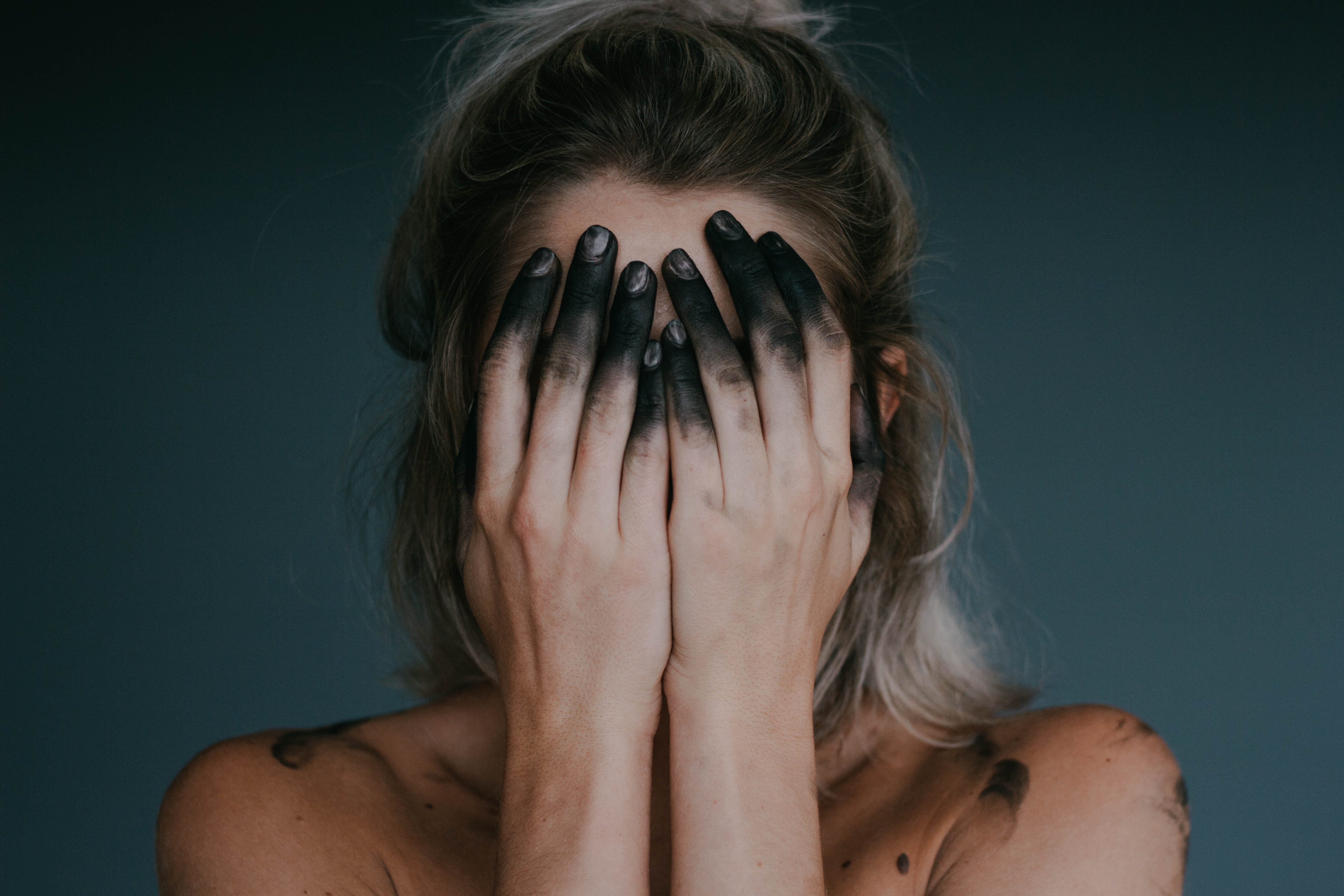 Woman covering her face. Tips of her fingers are covered in charcoal to represent feelings of burnout.