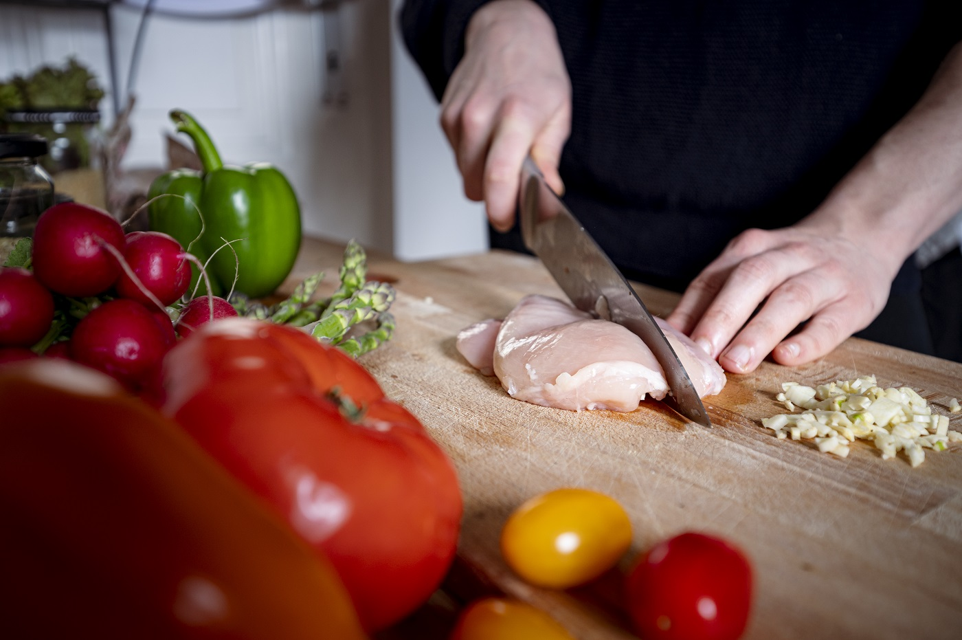 A person cuts a chicken fillet on a cutting board with a kitchen knife.
