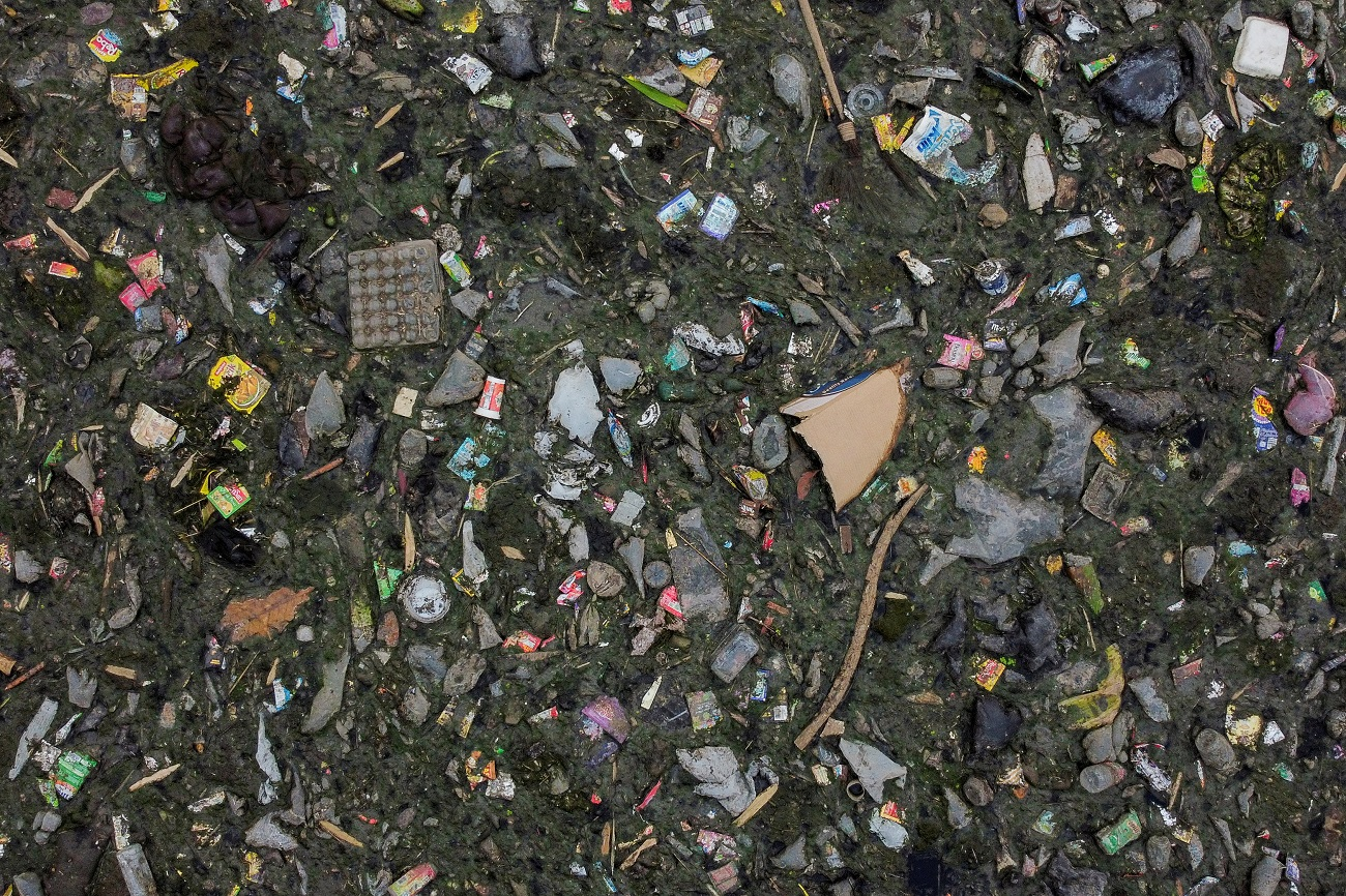 An aerial view shows domestic waste floating on the stream of the Citarum river in Bandung, Indonesia, March 15, 2021. The government has pledged to clean the Citarum river, considered among the world's most polluted, and make the water there drinkable by 2025, but household and industrial waste have continued to flow in its stream. Picture taken with a drone. REUTERS/Willy Kurniawan