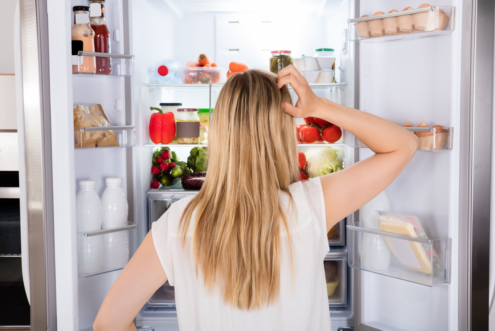 70309104 - rear view of young woman looking in fridge at kitchen