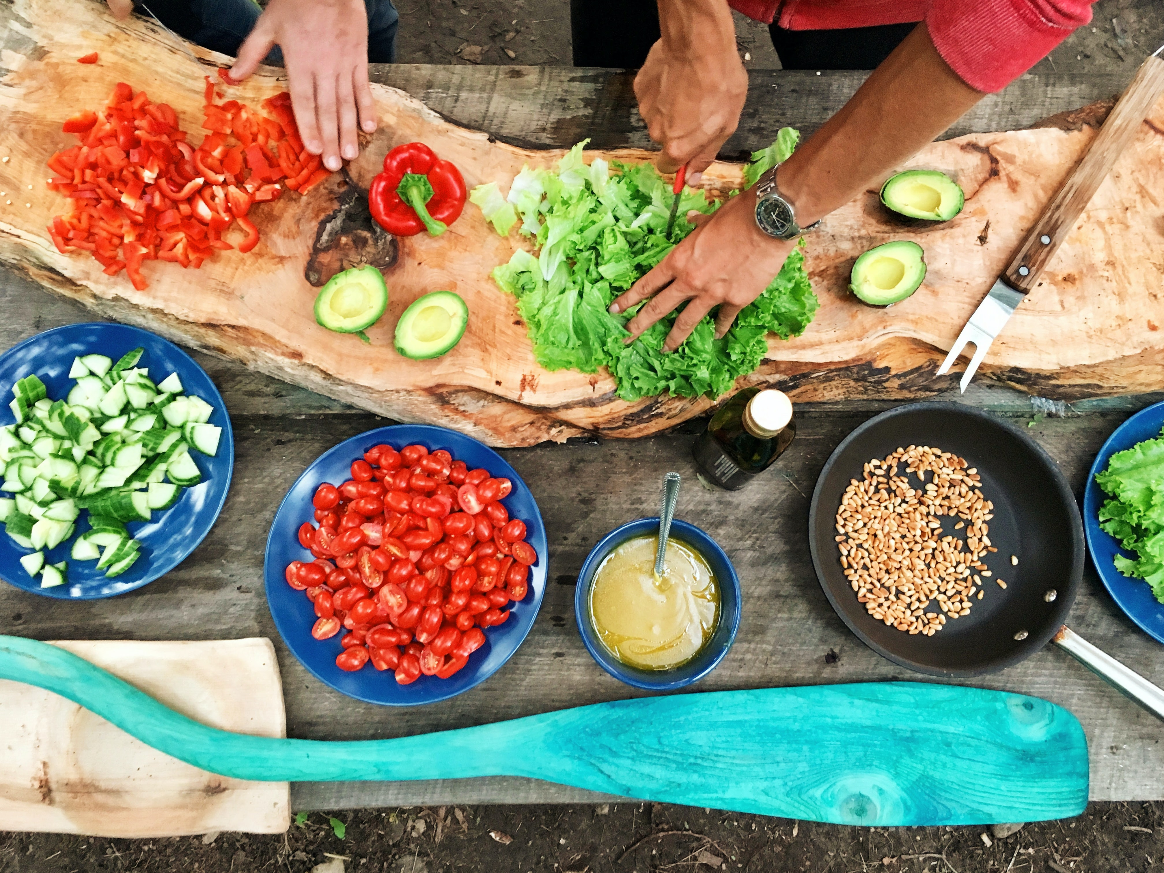 Images showing people cooking with lots of chopped vegetables