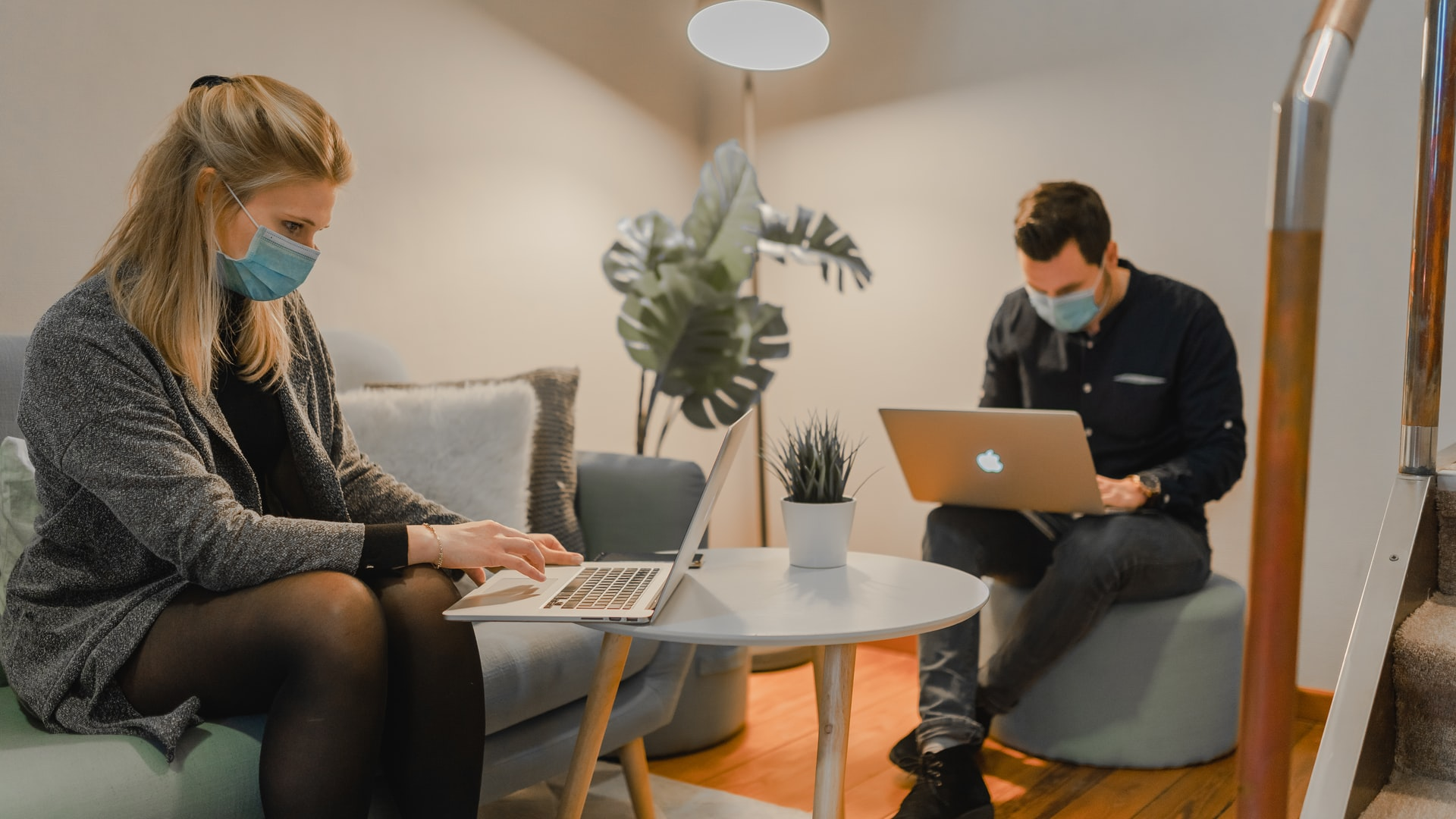two people working on couch with laptops