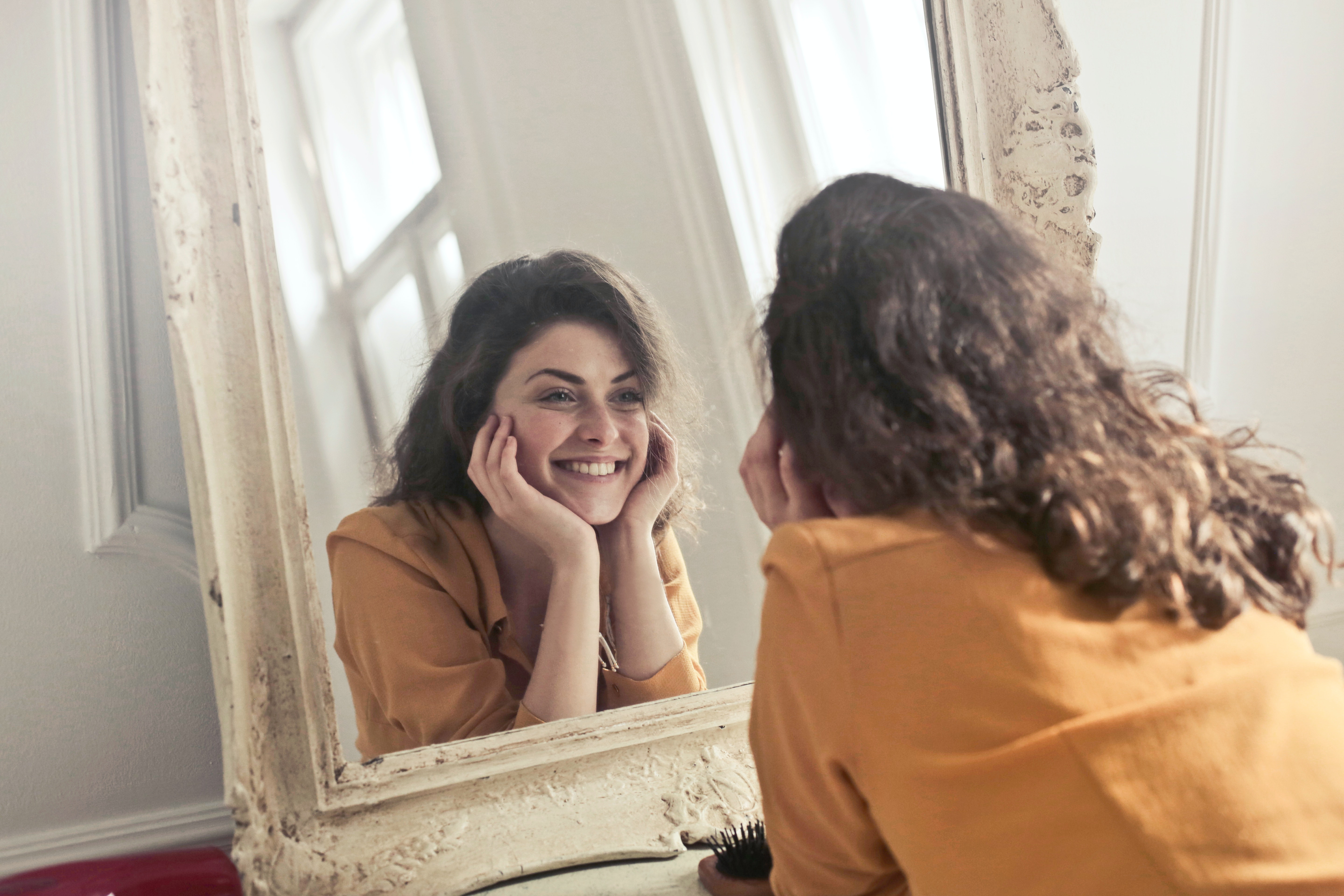 woman smiling looking into mirror