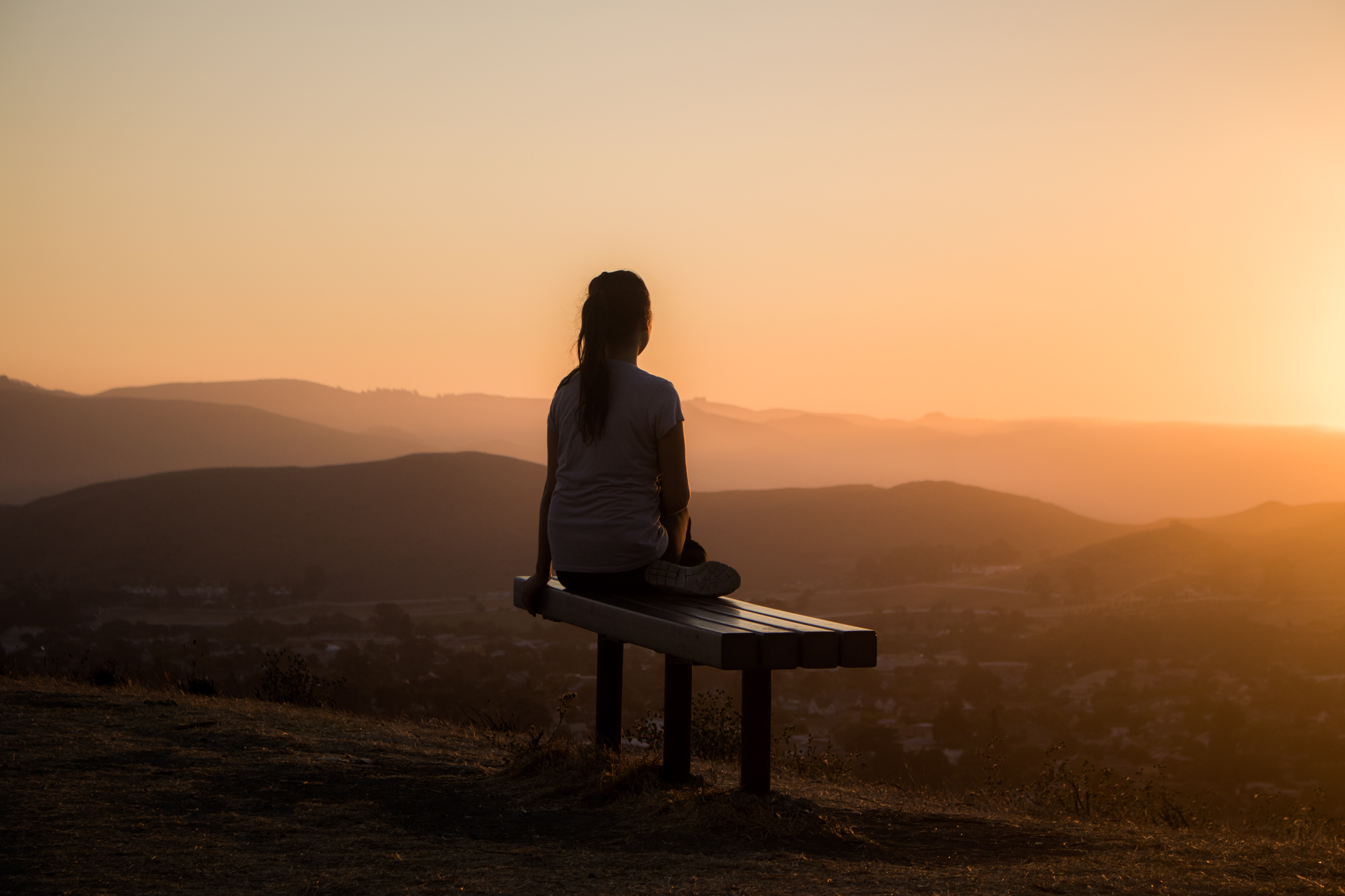 woman looking at the sunrise while meditating