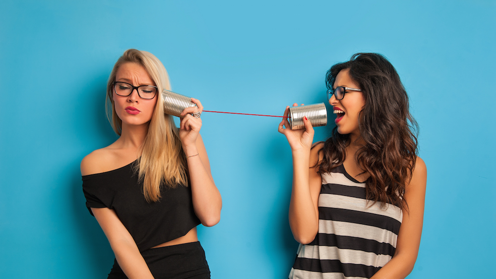 Blond and Brunette woman talking through can on Thrive Global for Brenda Della Casa's Article on Toxic Frienship
