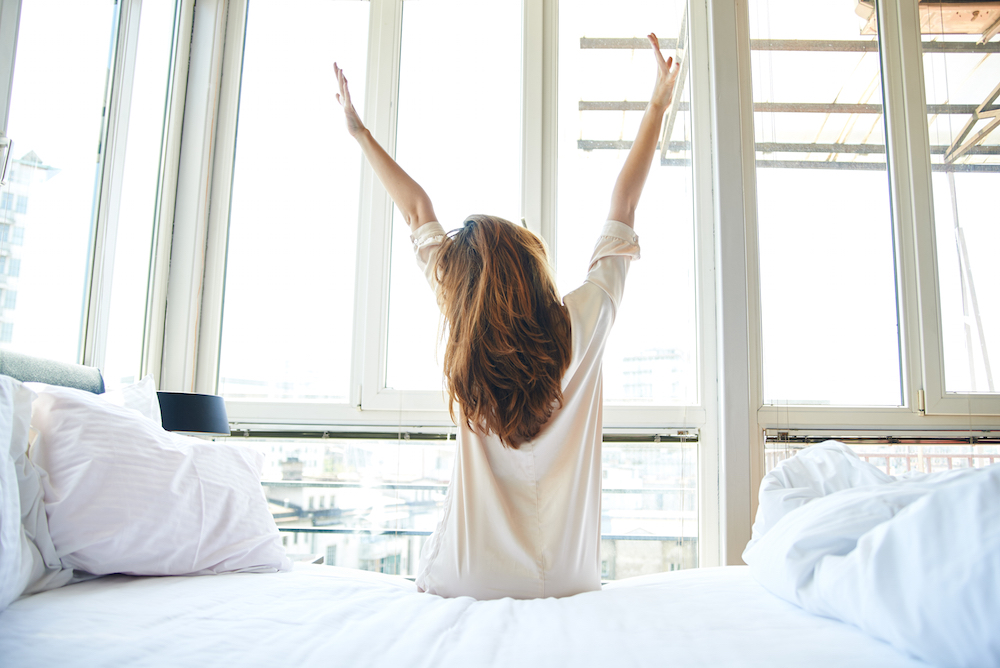 Woman stretching in bed by window for Brenda Della Casa's article on Thrive Global