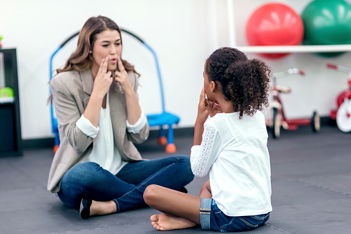 Adult female therapist guiding young girl in speech therapy for a therapy exercise
