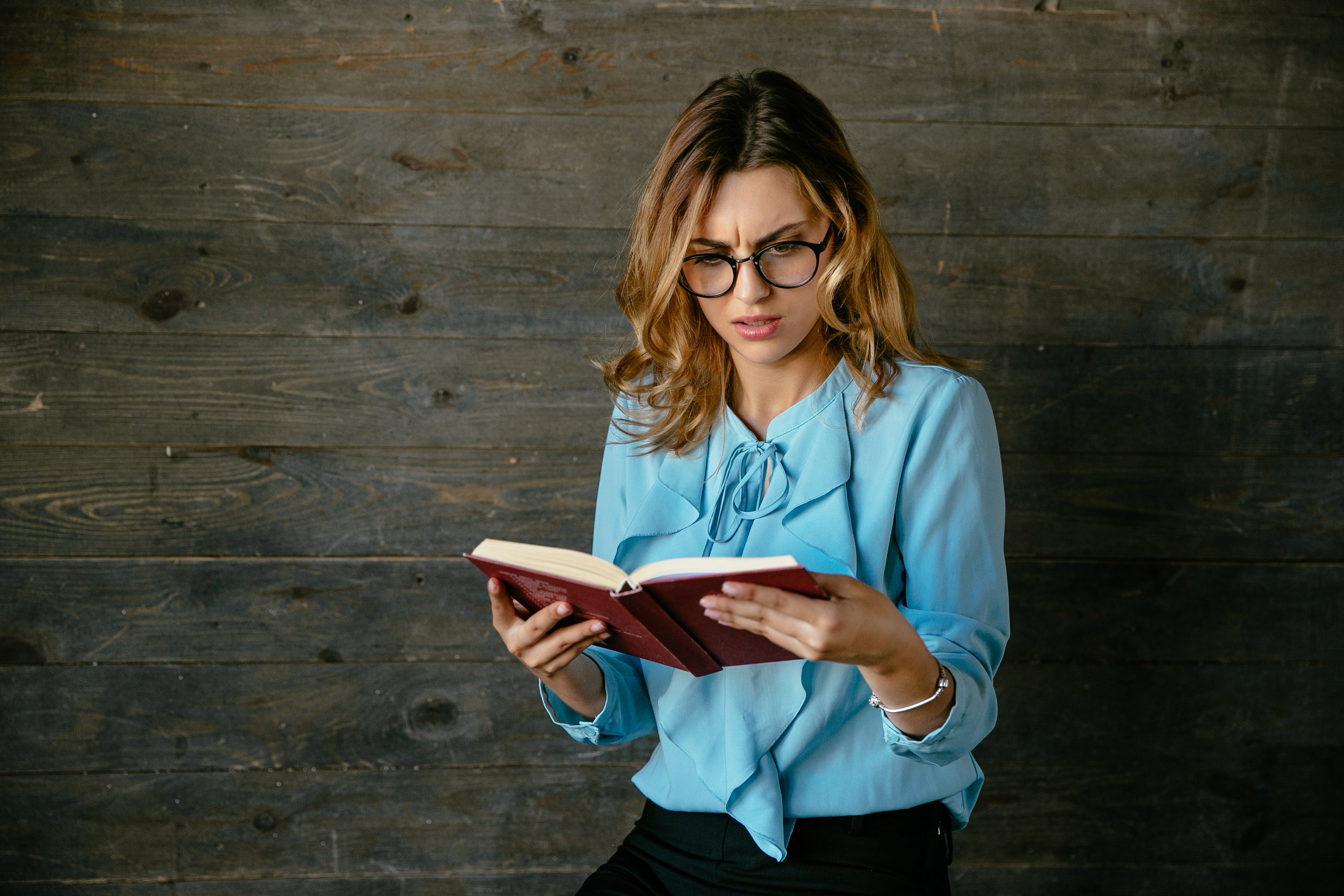 Attractive business woman looks confused while reading a book. Frowning her face in misunderstandment. Dressed in blouse, in eyeglasses.