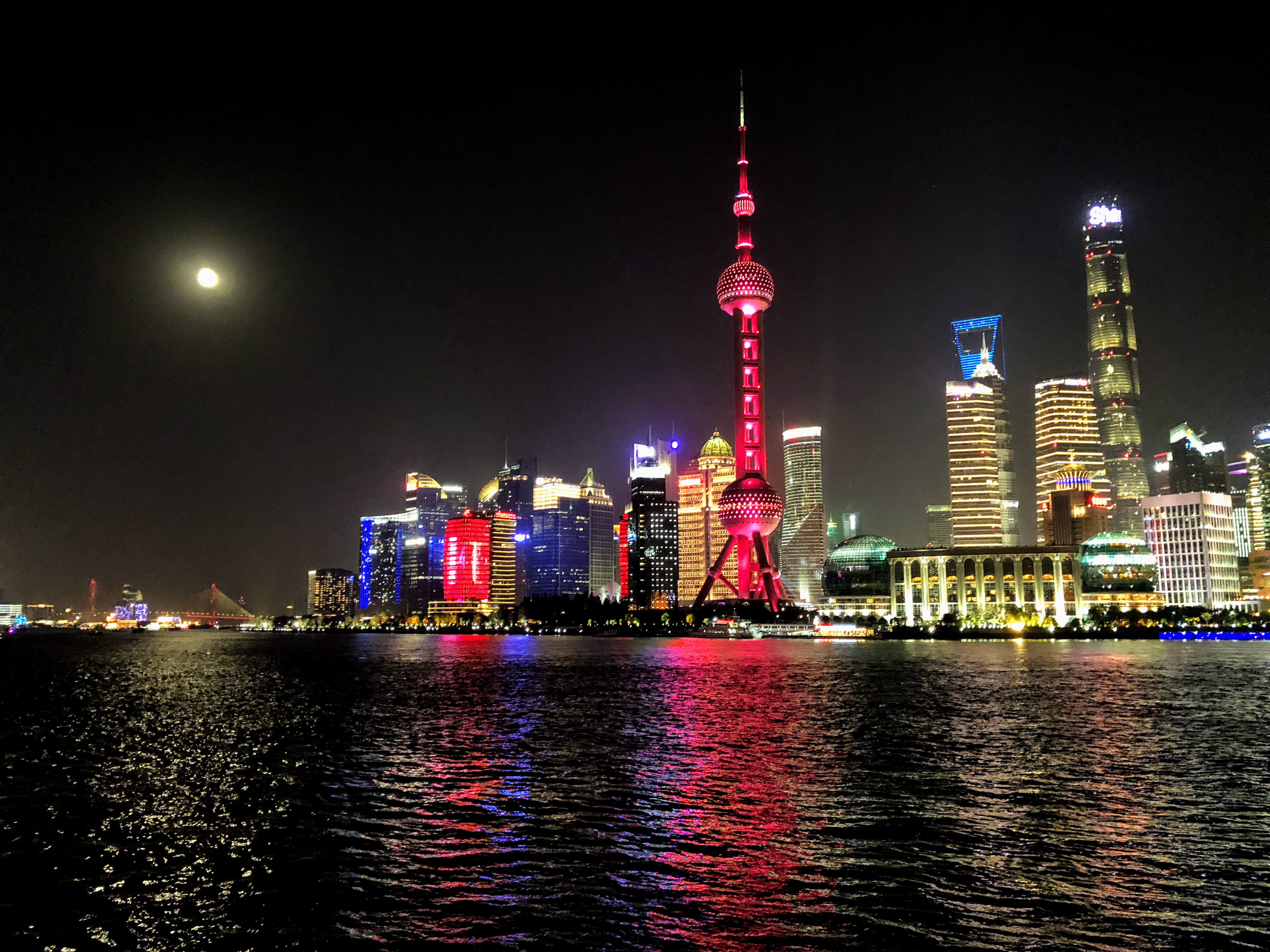 The Pearl Tower, and Shanghai Tower (second tallest in the world at 128 stories), pictured from across the Huangpu River on a full moon in Shanghai, China.