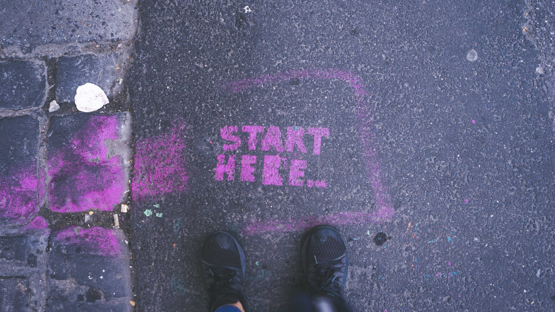 """Start Here"" in purple paint on the pavement"
