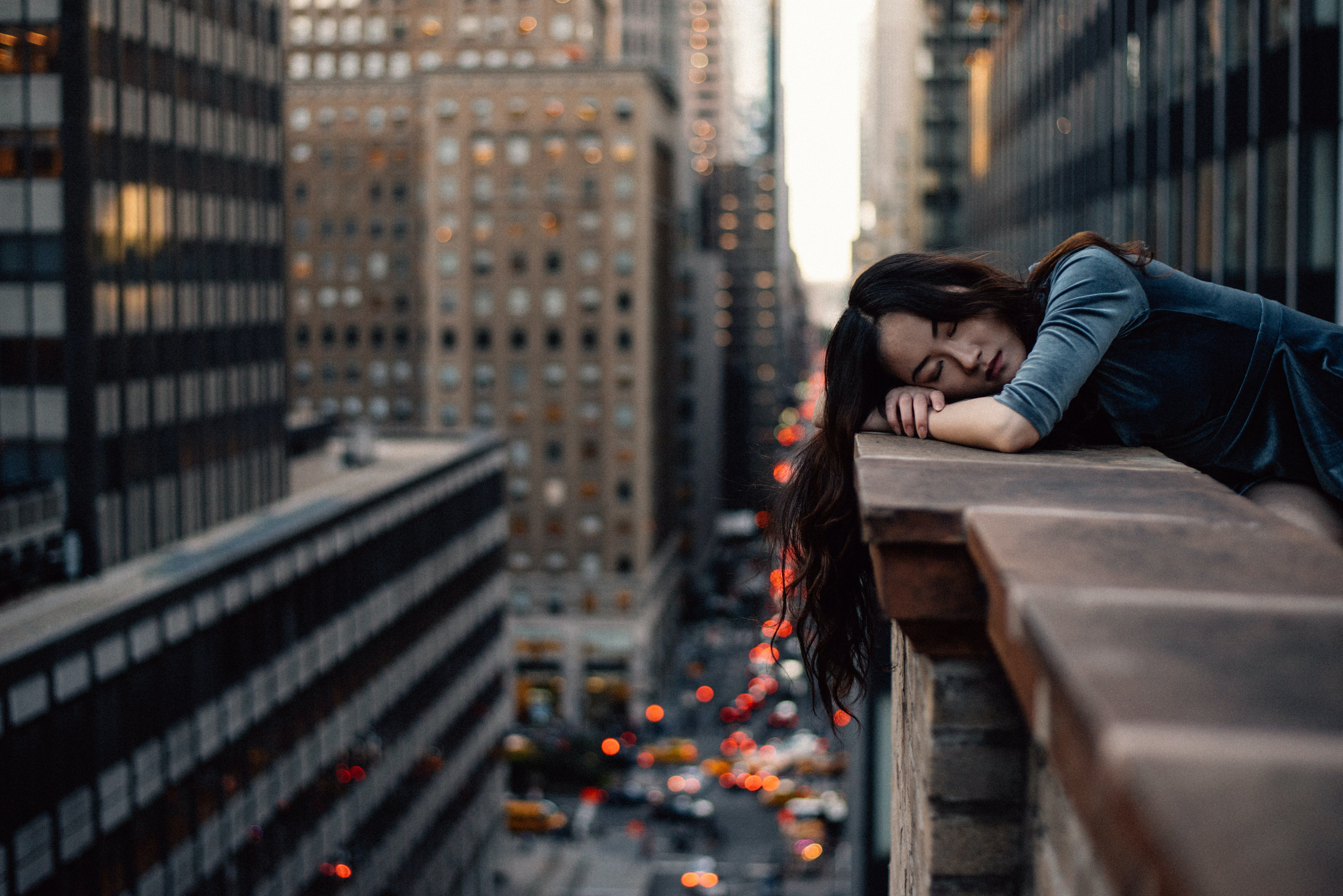 Tired woman resting her head on on a building roof.