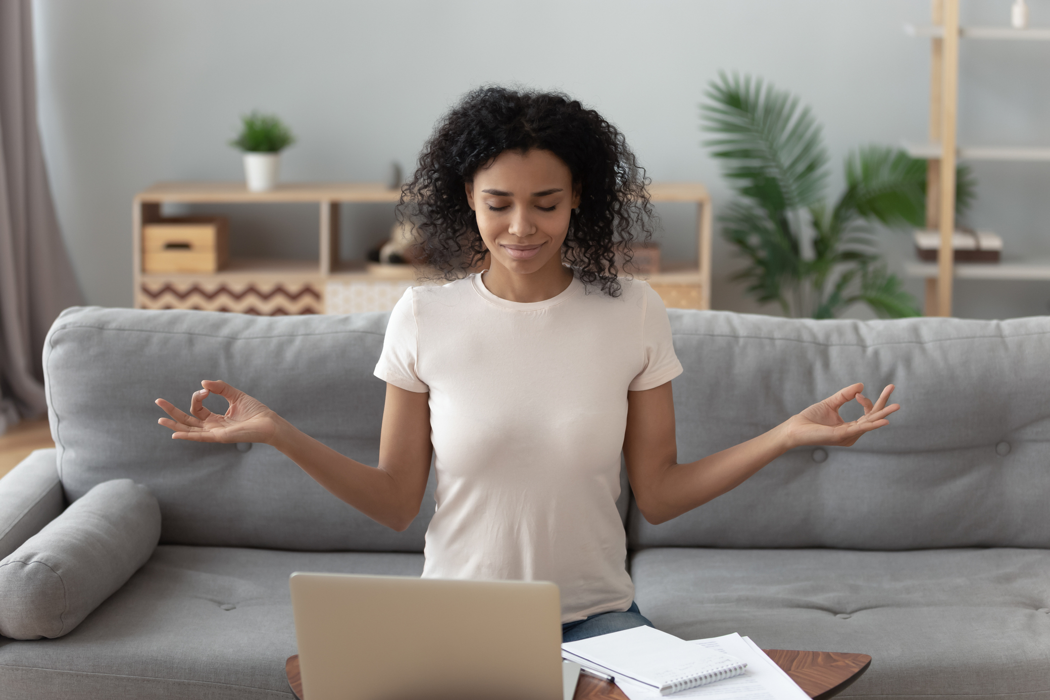 Serene happy calm african girl student sit on couch take break from computer work study do yoga exercise breath fresh air at home, mindful healthy woman relax meditating feel no stress free concept