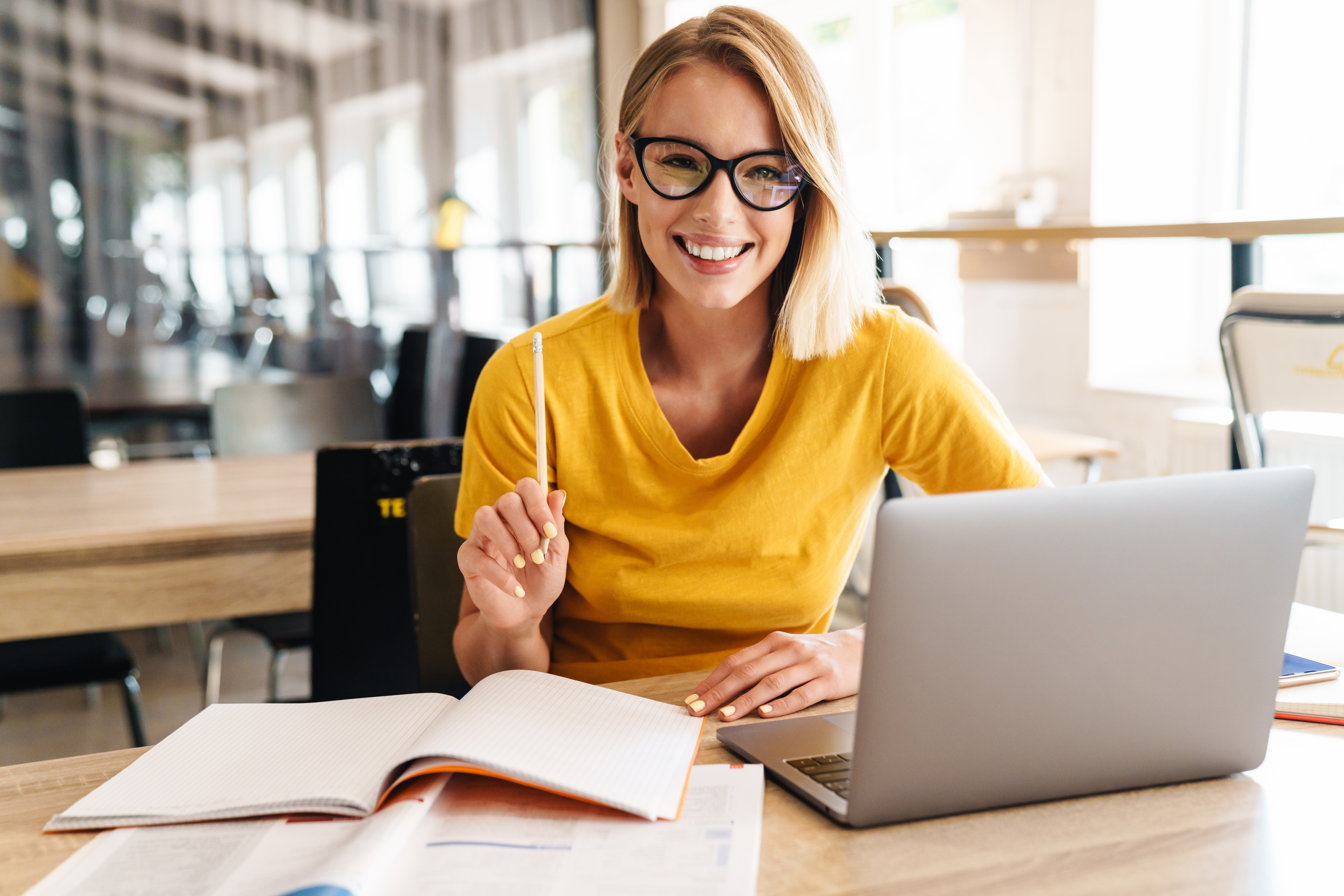 Photo of beautiful happy woman looking at camera while working and sitting at table in open-plan office