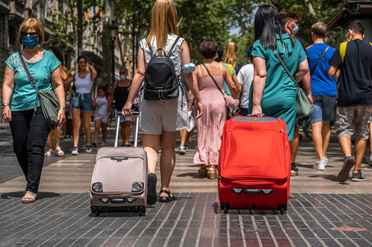 People are seen carrying rolling suitcases down the popular Rambla in Barcelona. Barcelona suffers the effects of the fifth wave of the coronavirus with more than 8,000 new cases in the last 24 hours, predominantly of the delta variant. New restrictive measures will be taken in the next few hours. (Photo by Paco Freire / SOPA Images/Sipa USA)