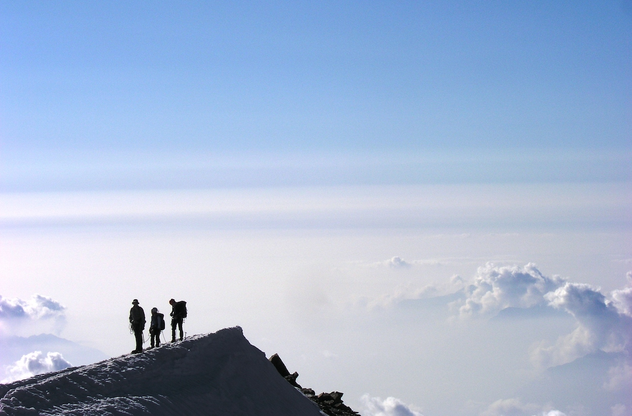 Three climbers on an icy ridge over the clouds