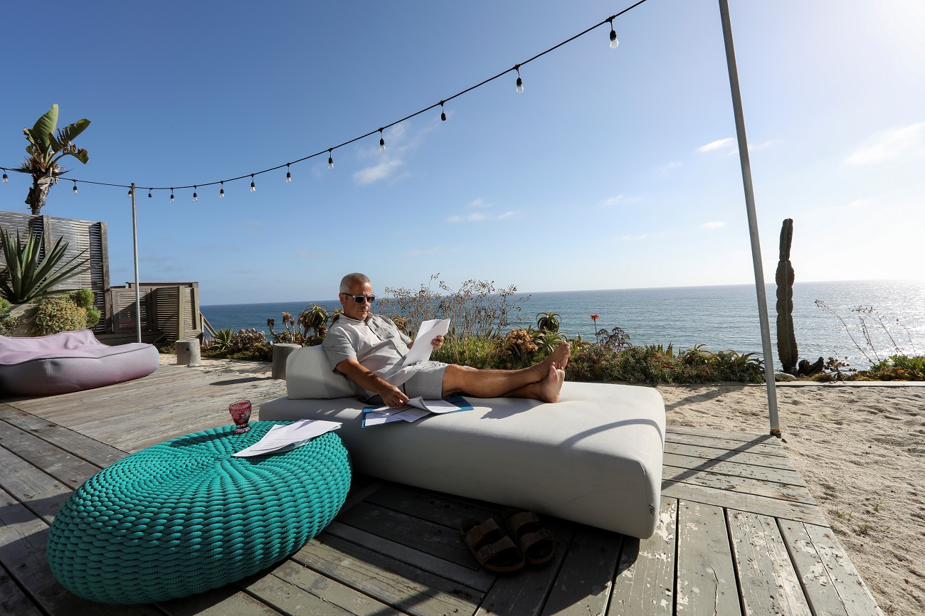 Michael Antonorsi, Chief Joy Activator at Chuao Chocolatier, goes over some documents as he works from his beachfront  home during the outbreak of the Coronavirus (COVID-19) in Leucadia, California, U.S., June 17, 2020. REUTERS/Mike Blake