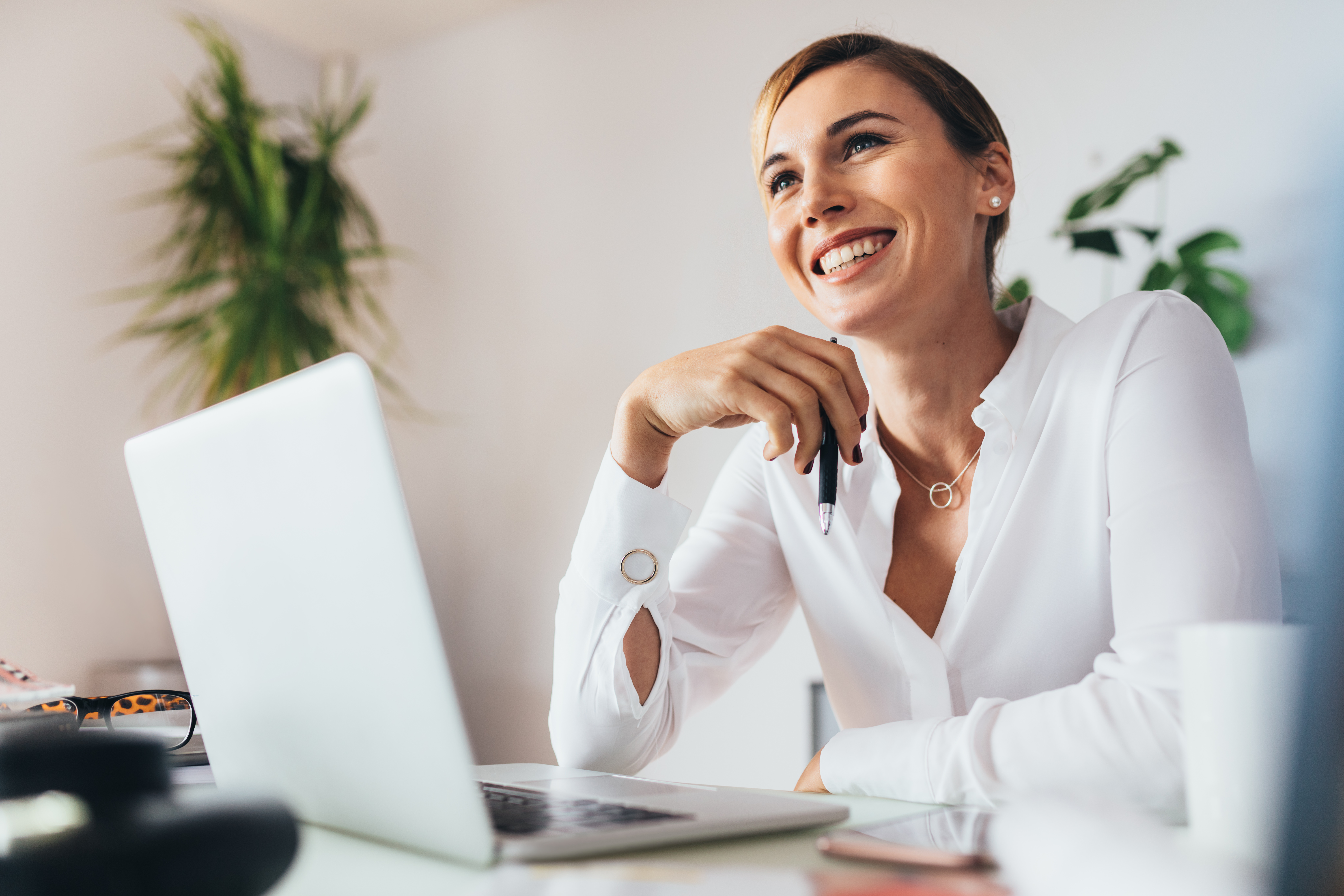 Smiling business woman sitting at her desk in office. Woman holding a pen with a laptop computer on her desk.