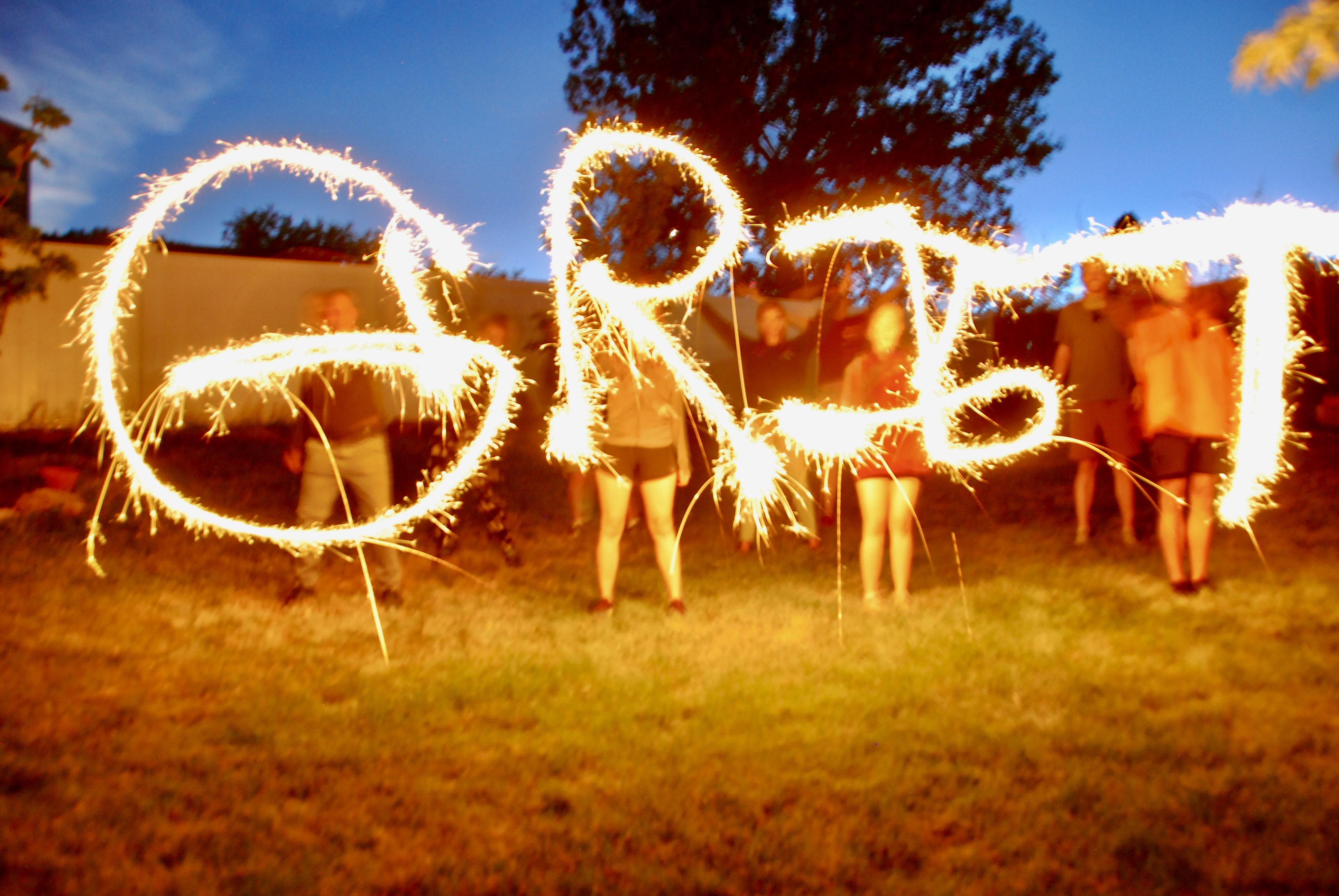 People holding sparklers spelling the word Grit