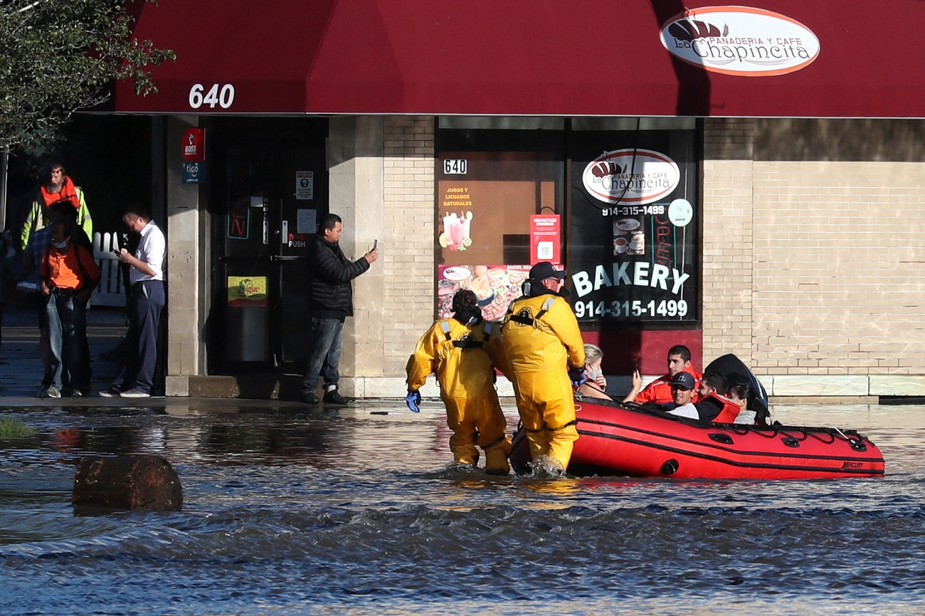 First responders pull local residents in a boat as they perform rescues of people trapped by floodwaters after the remnants of Tropical Storm Ida brought drenching rain,  flash floods and tornadoes to parts of the northeast in Mamaroneck, New York, U.S., September 2, 2021. REUTERS/Mike Segar