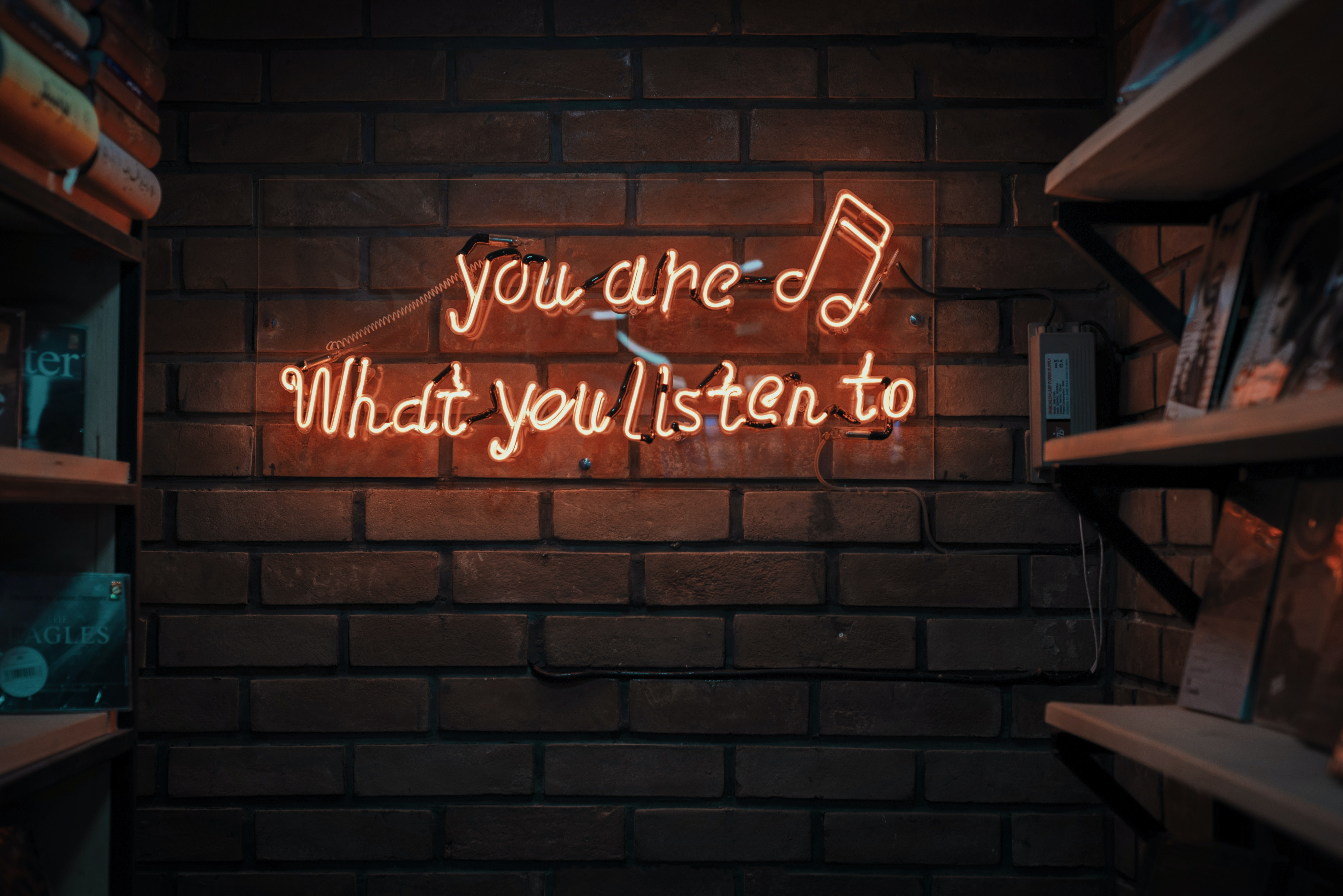 Photo of you are what you listen to text spelled in lights by music notes on brick wall. Photo on Dr. James Goydos 2021 article on physician health podcasts