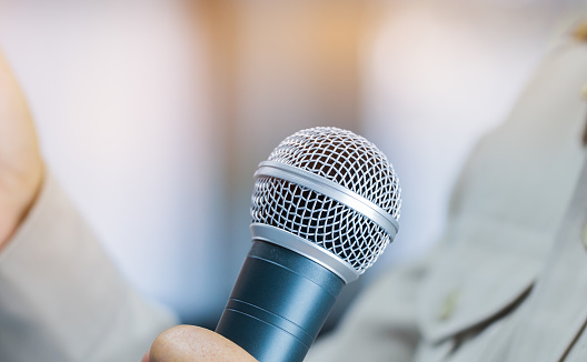 Smart Businesswoman speech or Speaking with microphone in Seminar hall, hand gesturing protesting or belief for explaining in conference room. Speaker tedtalk is vocalized form of communication humans