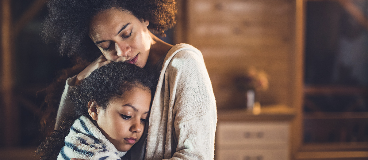 Black mother consoling her small daughter while embracing her at home.