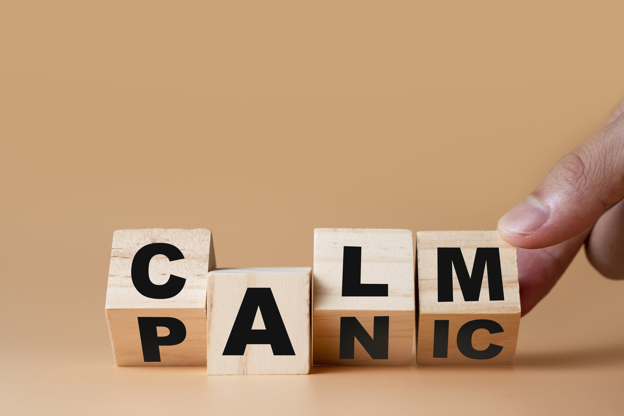 """Hand flipping wooden cubes for change wording"""" Panic """"  to """" Calm"""".  Mindset is important for human development."""