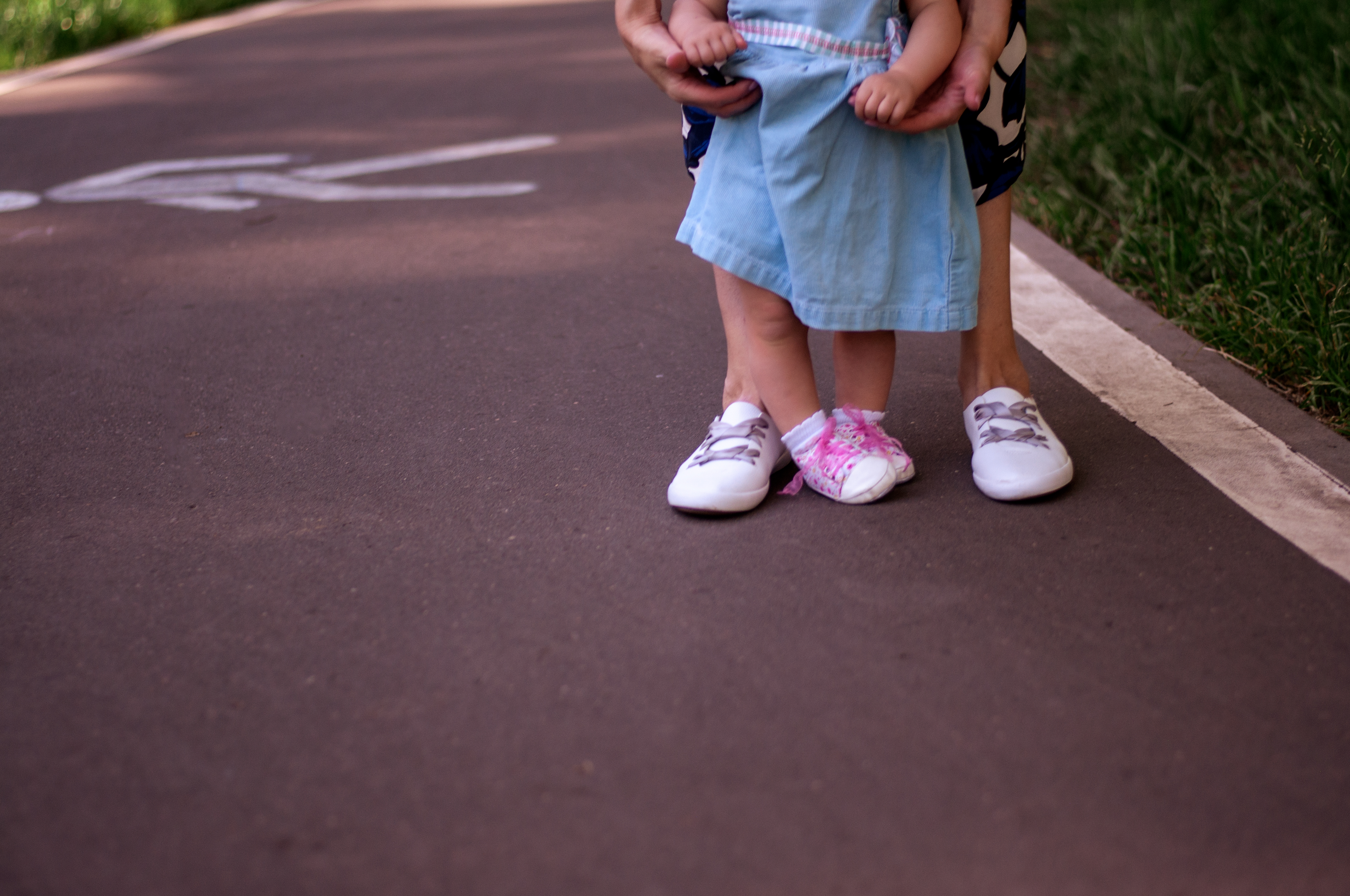 Mom teaches daughter to walk. Summer park, legs closeup. Mom with a one-year-old daughter in dresses are walking in the park. Teaching children, motherhood
